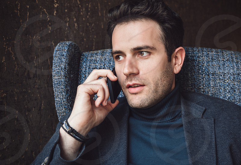 Young businessman talking at mobile phone sit on armchair. photo
