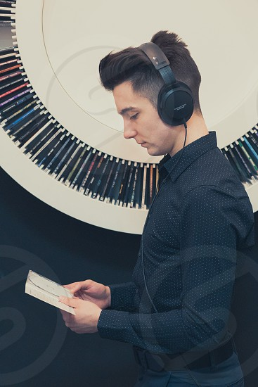 Young man listening to music through headphones standing next to bookshelf with recordings photo