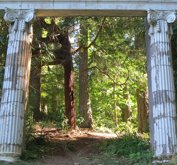Old stone arch leading to a path in a forest; Astoria Oregon photo