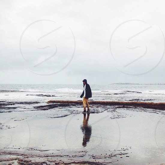 persons walking in water by the beach  photo