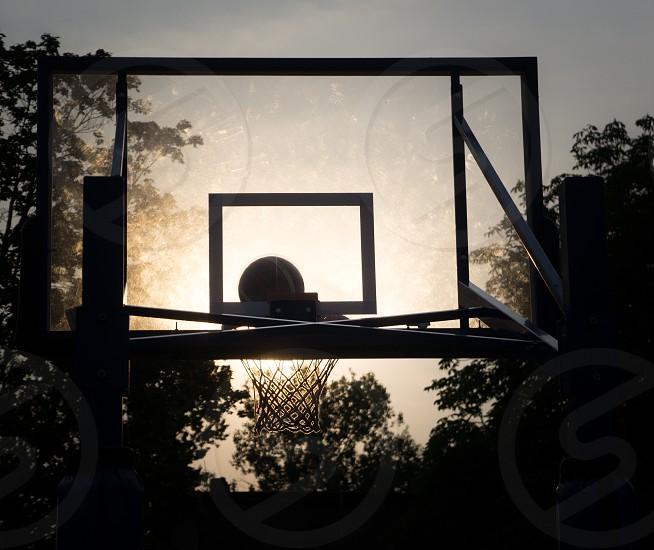 sun shining through the basketball hoop photo