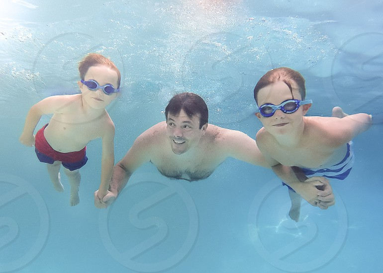 Dad and sons swimming underwater pool photo