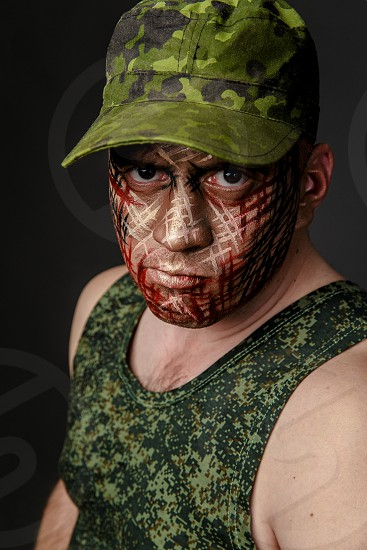 Portrait of Soldier with Military Style Camouflage on a  Face.  Portrait  on black background photo