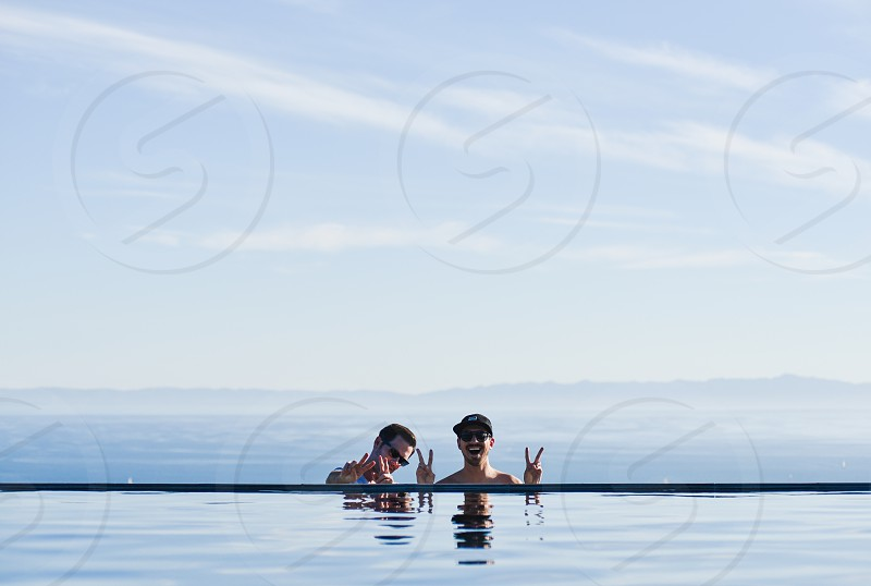 two men behind pool taking photo together with sea in background below white clouds and blue sky during daytime photo
