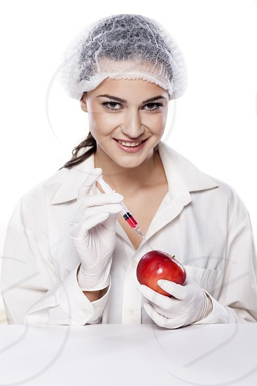 smiling chemist woman injected some liquid in red apple photo