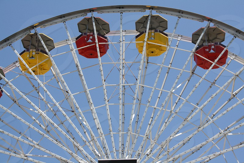 stainless steel ferris wheel with yellow and red seats photo