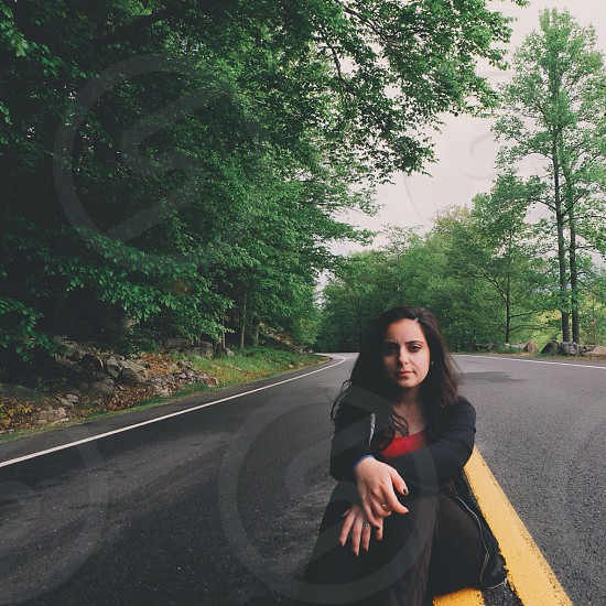 woman sitting in the middle of the road posing for camera shot photo
