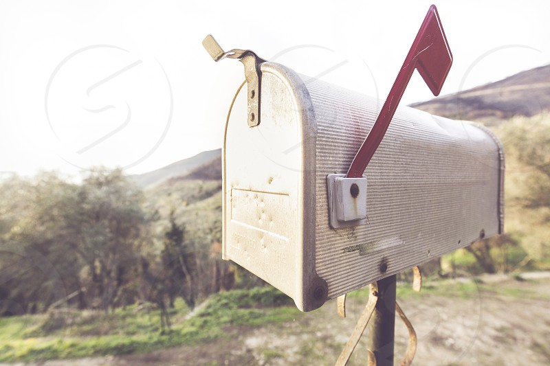 Metal mail box with typical American style behind you see a countryside landscape photo