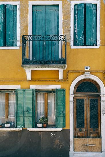 venice italy building facade doors windows shutters green photo