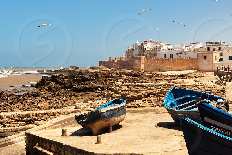 essaouira outdoor tower medieval landmarks destination coast historical town stone shore gate western travel walls view culture touristic moroccan port entrance africa traditional berber fortress wall morocco african architecture city buildings tourism ancient sea maroc water fortification arab coastline vacation ramparts arabic boats atlantic ocean harbor photo