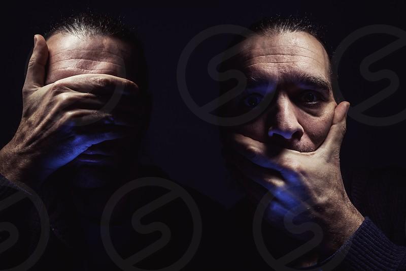 Men's eyes in dark ambient person with hood looking surprised.  photo