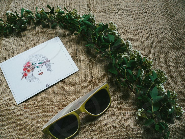 Sunglasses a sprig of flowers and a postcard photo