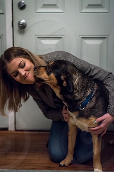 Woman greeting/saying goodbye to her dog upon arrival/departure at the front door. photo