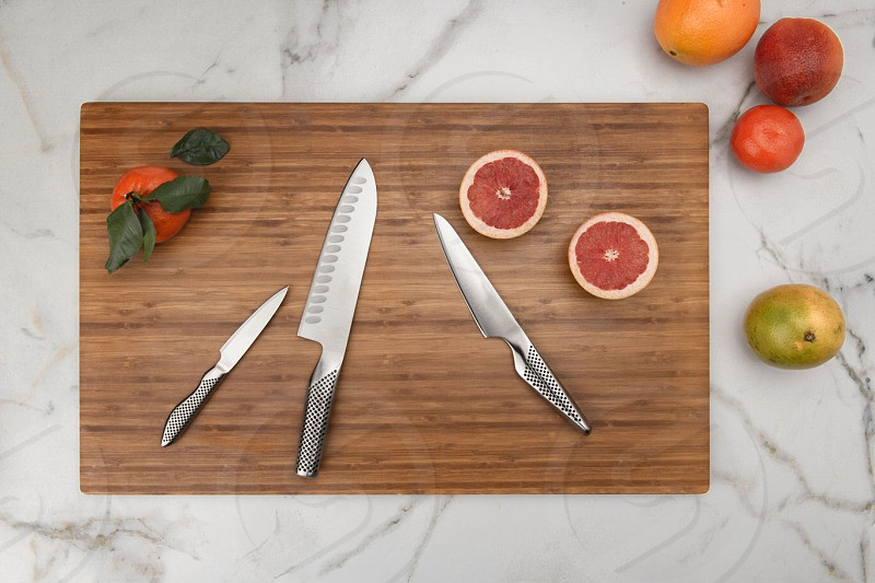 Overhead lifestyle knife set product photography on cutting board with marble background photo