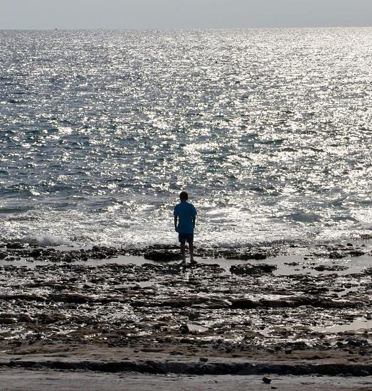 naturelandscapetravelauthenticexperiencesbeautifuloceanwatersunlightpeoplemanboystandinglookingview photo