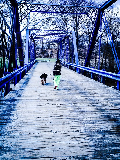 person with dog walking on a bridge photo