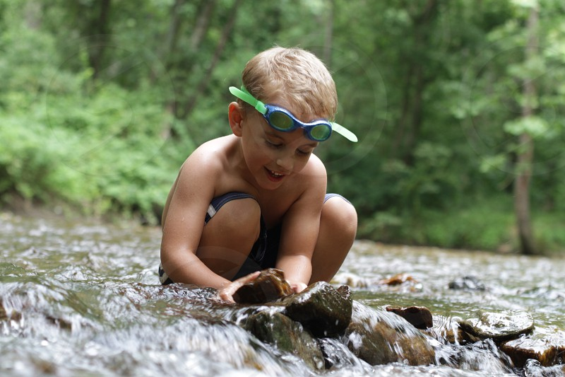 Lake water discovery build rocks stream outdoors goggles child learn learning young dam smile candid photo