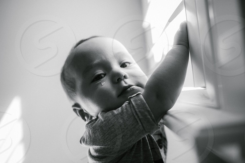 grayscale photo of baby standing near window photo