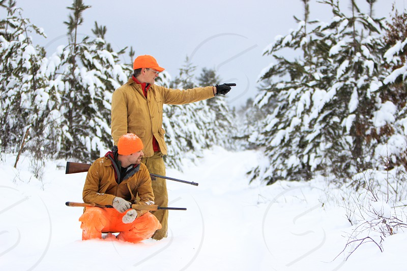 hunt hunters hunting man men father son legacy recreate recreation pastime outdoors outside winter snow cold trail trees forest pines evergreens white orange brown green safety gun firearm shotgun point direct show look photo