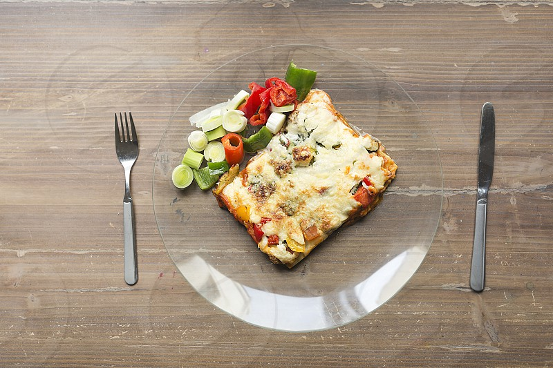 Vegetable lasagna in a glass dish on a wooden background. photo