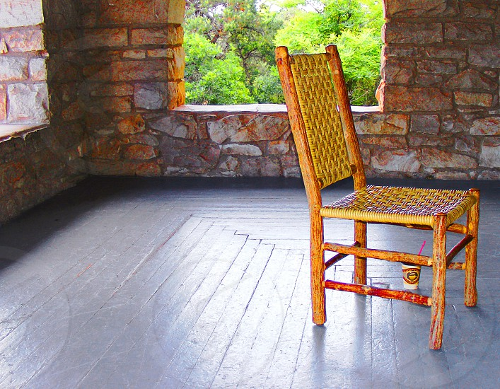 Rustic wicker chair sits on a porch of a stone house photo