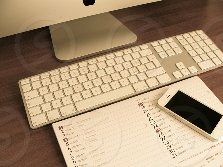 silver apple computer keyboard on brown wooden surface photo