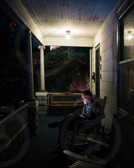 man sitting on porch rocking chair photo