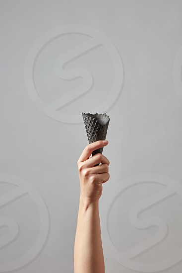 A female hand holds an empty black wafer cone on a gray background with a copy space. Layout for your business ideas photo