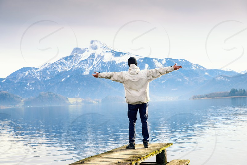A man standing on a wooden pier with raised hands up against the background of mountains and lake success photo