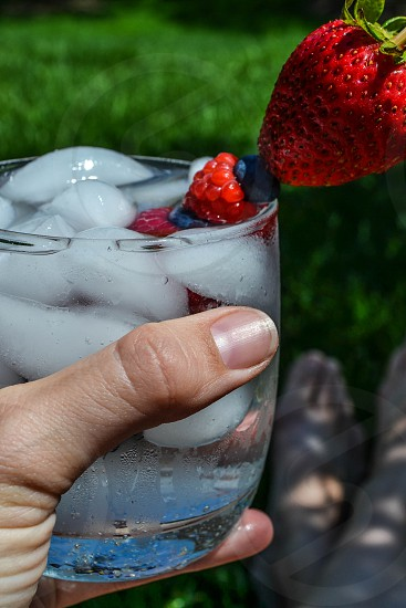 sitting in the grass enjoying a summer cocktail with berry garnish photo