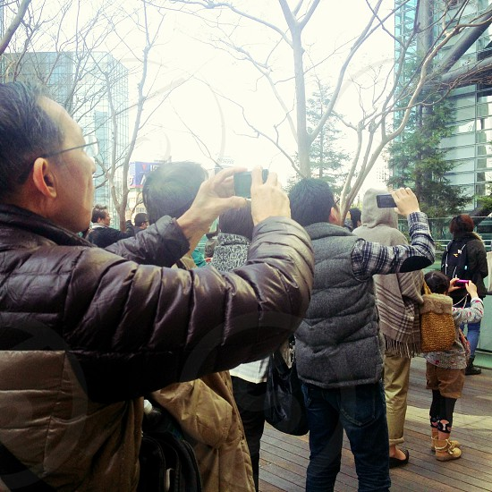 group of people standing outdoors holding cameras photo