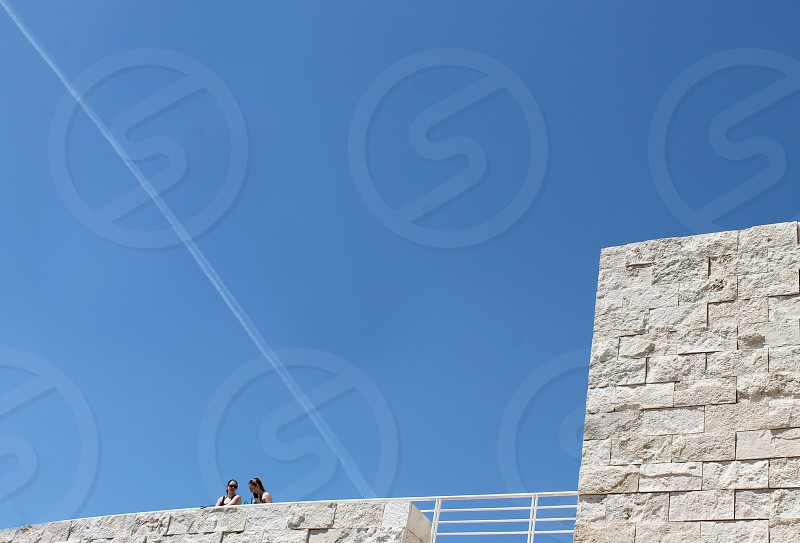 A contrail forms a triangular frame around two people standing on a terrace of a tall building. photo