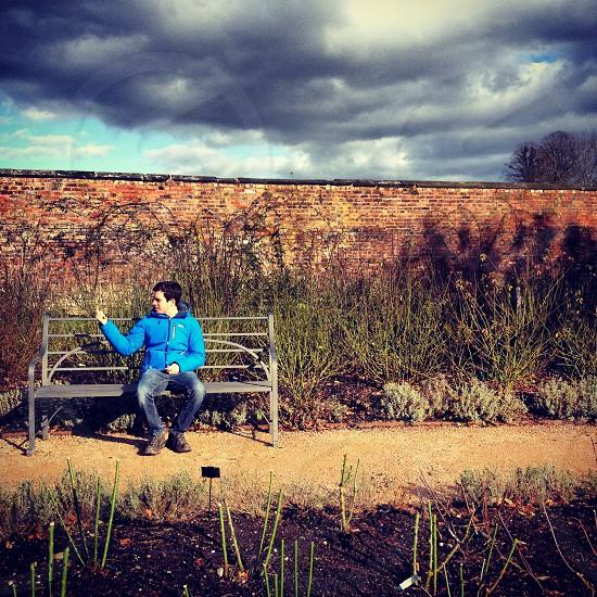 dark clouds under a man sitting on a metal bench photo