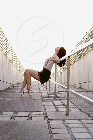 woman in ballet toe shoes leaning on a railing photo