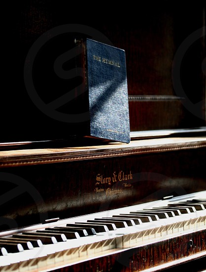 blue hymnal book on wood piano photo