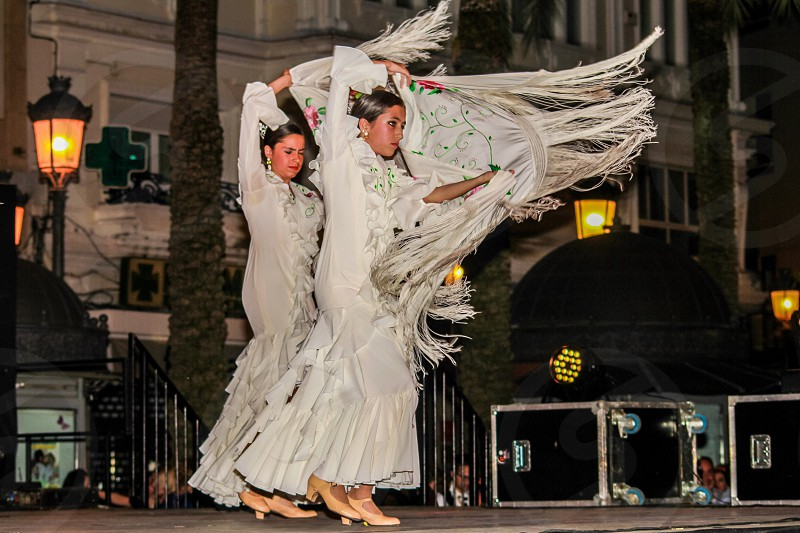 photo of 2 woman wearing white long sleeve ruffle fringe long dress dancing on the stage near white concrete building during noghttime photo
