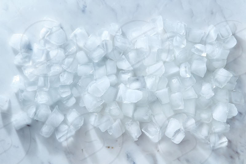 Clean cold ice cubes on a gray marble background. Ingredient for summer cooling drink. Flat lay photo