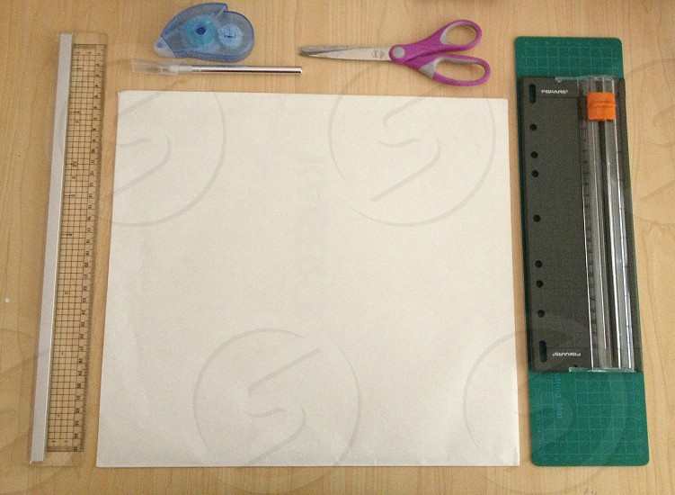 white paper scissors and ruler on table photo