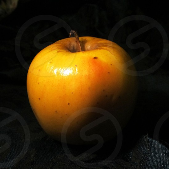 Yellow apple on black background  photo