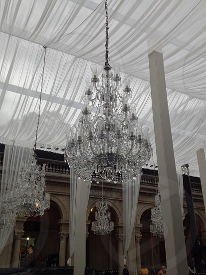 silver and cut glass uplight chandeliers on ceiling near white pillar photo