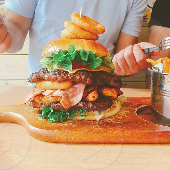 person in grey shirt with stainless steel fork behind hamburger on brown board beside stainless steel bucket on beige wooden table photo