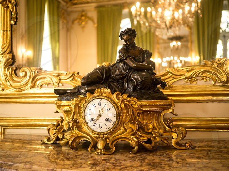 ornate white and gold room in French chateau sculpture of woman on a gold clock with chandelier in the background gilded gold mirror photo