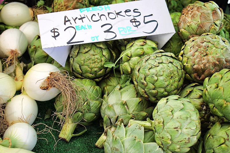 Artichokes and a few onions for sale at a farmer's market photo