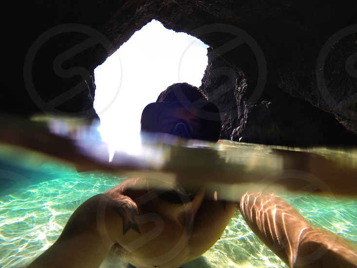 man in goggles on water underneath cave photo