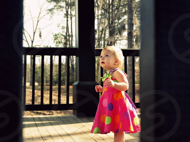 girl wearing a pink polka dot dress looking up photo