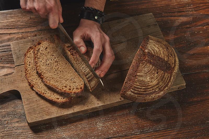 Baker Slicing Bran Bread on a wooden Board photo