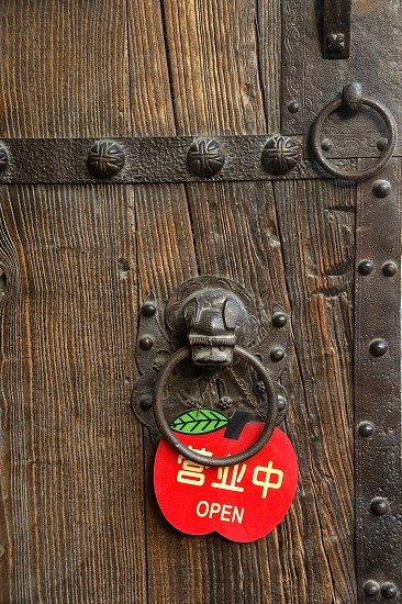 finely decorated chinese wooden old door with a red open sign photo