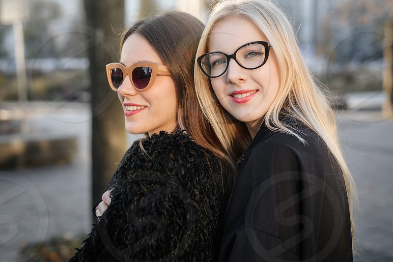 Two pretty girls hug each other on the city street and smile photo