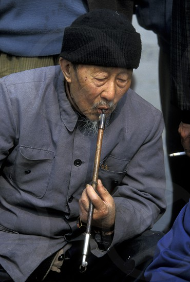 a chinese men smoking a traditional pipe in a parc in the city of Chengdu in the provinz Sichuan in centrall China. photo