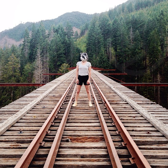 person in white blouse wearing racoon mask standing on bridge photo